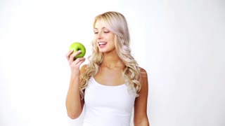 healthy food, fruits, diet and people concept - happy beautiful young woman eating green apple