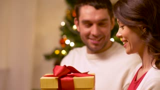 holidays, celebration and people concept - happy couple with christmas gift at home