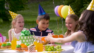 holidays, childhood and celebration concept - happy friends giving presents to birthday child at summer garden party