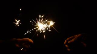holidays, pyrotechnic and christmas concept - hands with burning sparklers in darkness