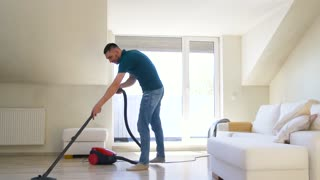 household and cleaning concept - man with vacuum cleaner at home