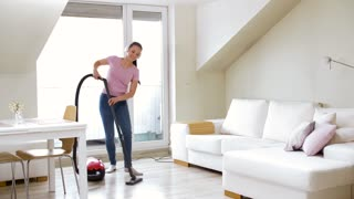 household, housework and cleaning concept - happy woman or housewife with vacuum cleaner and headphones dancing and singing at home