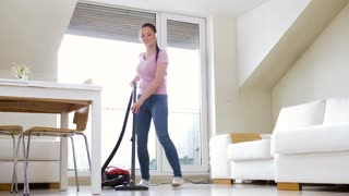 household, housework and cleaning concept - happy woman or housewife with vacuum cleaner and headphones dancing at home