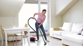 household, housework and cleaning concept - happy woman or housewife with vacuum cleaner dancing at home