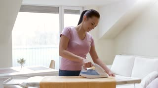 housework and household concept - happy woman or housewife ironing bath towel on iron board at home