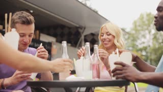 leisure, celebration and people concept - friends clinking bottles of non-alcoholic drinks and eating wok at food truck