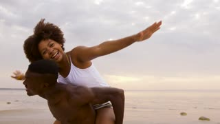 leisure, freedom and people concept - happy couple having fun on summer beach
