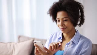 leisure, technology and people concept - smiling woman with smartphone and headphones sitting on couch and listening to music at home