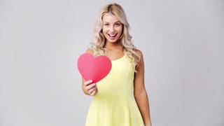 love, romance, charity, valentines day and people concept - smiling young woman in dress with red paper heart