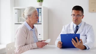 medicine, age, healthcare and people concept - ill senior woman and doctor with clipboard meeting at hospital