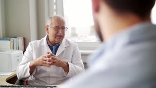 medicine, healthcare and people concept - senior doctor talking to young male patient having health problem at hospital