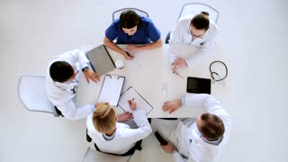 medicine, healthcare, people and cardiology concept - group of doctors with cardiogram on clipboard at hospital