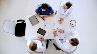 medicine, healthcare, people and cardiology concept - group of doctors with clipboards and cardogram discussing medical report at hospital