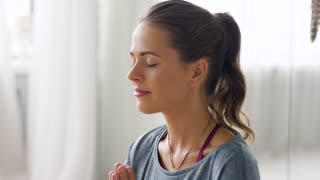 mindfulness, spirituality and healthy lifestyle concept - woman meditating at yoga studio