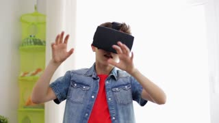 modern technology, gaming and people concept - boy in virtual reality headset or 3d glasses playing videogame at home