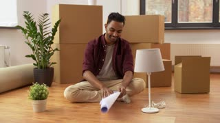 moving, people and real estate concept - happy indian man with boxes and blueprint at new home