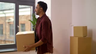 moving, people and real estate concept - happy indian man with boxes dancing at new home
