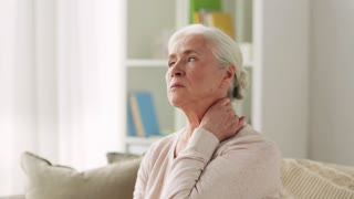 old age, health problem and people concept - senior woman suffering from neck pain at home