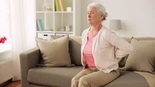 old age, health problem and people concept - senior woman suffering from pain in back or reins at home