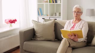 old age, leisure and people concept - senior woman in glasses reading book at home