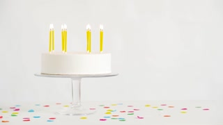 party and festive concept - birthday cake with burning candles on table