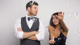 party, fun and holidays concept - happy woman dancing in soap bubbles next to bored man