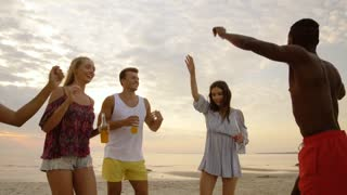 party, summer holidays and people concept - group of happy friends with non alcoholic drinks dancing on beach