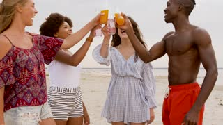 party, summer holidays and people concept - happy friends clinking bottles of non alcoholic drinks on beach