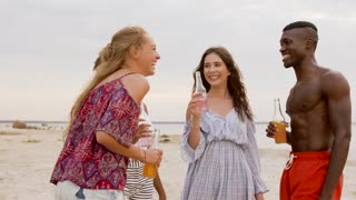 party, summer holidays and people concept - happy friends with bottles of non alcoholic drinks talking on beach