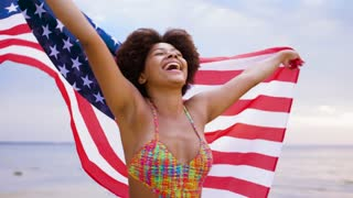 patriotism, independence day and holidays concept - happy smiling young african woman in swimsuit with national american flag on summer beach