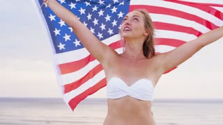 patriotism, independence day and holidays concept - happy smiling young woman in bikini with national american flag on summer beach