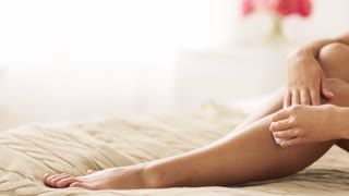 people, beauty, epilation and bodycare concept - beautiful woman with epilator removing hair from legs sitting on bed at home bedroom