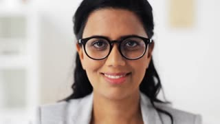 people, business, emotion and facial expression concept - face of happy smiling young woman in glasses