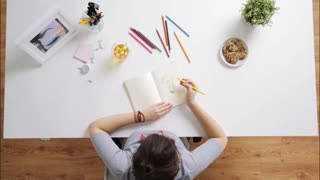 people, creativity and art concept - woman or artist drawing picture of light bulb in notebook and drinking iced tea at home desk