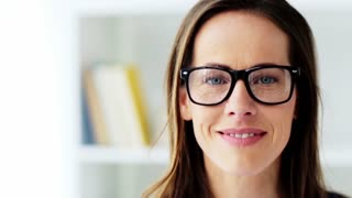 people, emotion and facial expression concept - face of happy smiling middle aged woman in glasses