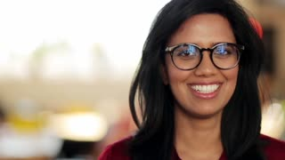 people, emotion and vision concept - face of happy smiling young woman in glasses