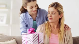 people, family, holidays and birthday concept - happy girl giving present to mother at home