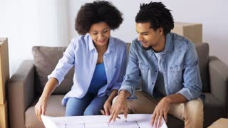 people, moving, repair and real estate concept - happy couple with blueprint and boxes at new home