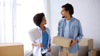 people, repair and real estate concept - smiling couple with cardboard boxes and lamp moving in or out of home