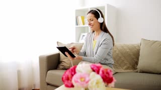 people, technology and leisure concept - happy woman sitting on sofa with tablet pc computer and headphones listening to music at home