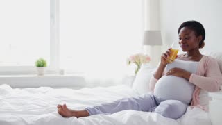 "pregnancy, ""healthy eating"", diet and people concept - happy pregnant african american woman drinking fresh orange juice in bed"