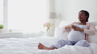 pregnancy, people and rest concept - happy pregnant african american woman stretching in bed at home bedroom