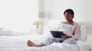 pregnancy, technology and people concept - happy pregnant african american woman with tablet pc computer in bed at home