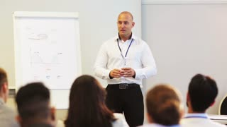 renewable energy, business and power concept - businessman or engineer with charts on whiteboard and wind turbine model speaking to group of people at conference presentation