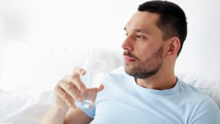 rest and people concept - man drinking water in bed at home
