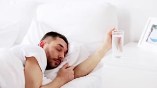 rest, sleeping and people concept - man waking up and drinking water in bed at home