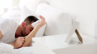 rest, sleeping and people concept - man waking up in bed at home