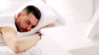 rest, sleeping and people concept - man with smartwatch waking up in bed at home