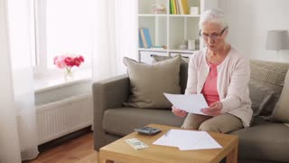 savings, annuity insurance, old age and people concept - senior woman with calculator and bills counting dollar money at home