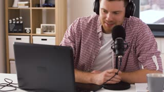 technology, audioblog and gaming concept - young man in headphones with laptop computer speaking to microphone, ending broadcast and leaving room